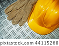 Safety gloves hard hat on corrugated metal sheet 44115268