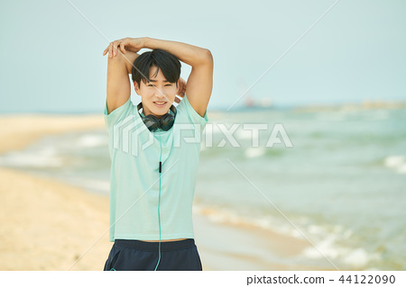 Male, young man, exercise, stretching, earphones, beach 44122090
