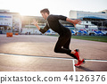 athlete in black clothes starting sprint on running track 44126376