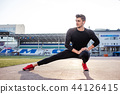 man stretches the body before running on race track in stadium 44126415