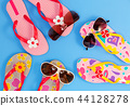 Beautiful flip flops with sunglasses on blue paper 44128278