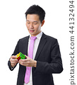 Asian businessman with a puzzle game on white bac 44132494