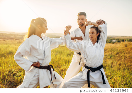 Two female fighters on karate training with master 44135945