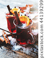 Mugs of mulled wine with autumn leaves and snow. 44139299