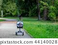 baby boy in a stroller in a park. 44140028