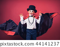 Halloween vampire boy waves his black, red cloak with his hands surrounded on red studio background. 44141237