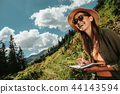 Cheerful girl in sunglasses making notes in the forest 44143594
