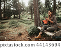 Young cheerful lady listening music on smartphone in the forest 44143694