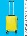 Yellow plastic luggage isolated on blue background with clipping path on suitcases object 44149803