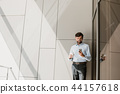 Grinning businessman is using phone during free time 44157618