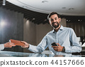 Cheerful man is taking account from receptionist 44157666