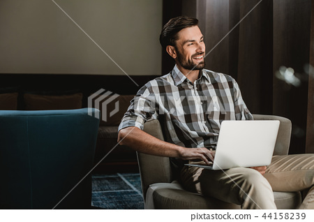 Delighted guy is having fun with laptop indoor 44158239