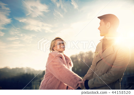 Happy young couple holding hands under beautiful sky 44158520