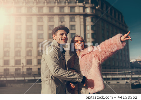 Blond girl pointing at something interesting while having date with boyfriend 44158562