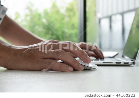 Hand are using the mouse and keyboard. 44160222