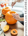 Woman's hand with knife cuts pumpkin for Halloween 44164981