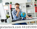 A young man sits in the office at a computer desk and in front of him stands a globe. 44165999