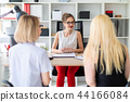 A young girl sits at a table in her office and talks to two co-partners. 44166084
