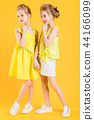 The girls of the twins stand together on a yellow background. 44166099