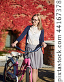Attractive blond girl at pink lady bicycle on sunny day on wall overgrown with red ivy background. 44167378