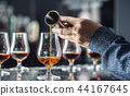 Bartender hand pouring alcoholic drink in pub. 44167645