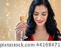 Young woman holding a champagne flute 44168471
