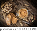 Glass jar with peanut butter on wooden background 44173398