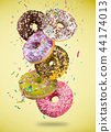 Tasty doughnuts in motion falling on pastel yellow background. 44174013