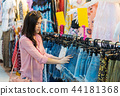 woman choosing and buying shorts in shopping store 44181368