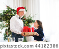 A senior man with a Santa hat giving presents to a small girl at Christmas time. 44182386