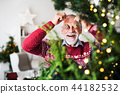 A senior man standing by Christmas tree, putting balls in front of eyes. 44182532