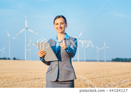 Investor in wind turbines with computer evaluating her investment 44184127
