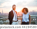 Two businesspeople standing against London rooftop view at sunset. 44194580