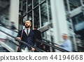 Hipster businessman using escalator in city, travelling to work. 44194668