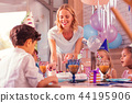 Smiling woman leaning to the table and giving cake to the boy 44195906