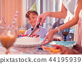 Happy birthday boy smiling while looking at the process of slicing cake 44195939