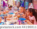 Three children sitting silently while eating tasty food 44196011
