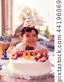 Cute birthday boy wearing party hat and sitting with cake 44196069