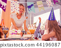 Kind mother smiling and putting big cake on the table 44196087