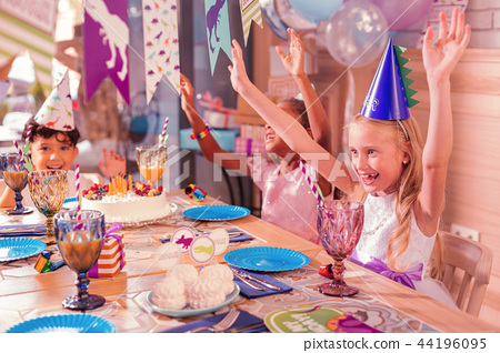Excited kids putting hands up and dancing at the table 44196095