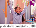 Happy boy sitting at the table and putting hands up at the party 44196100