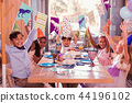 Emotional kids putting hands up while sitting at the table 44196102
