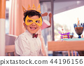 Happy boy wearing paper mask and looking ready for party 44196156