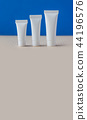 Hygiene cosmetic tubes on blue and beige background. Three blank white plastic containers, simple 44196576