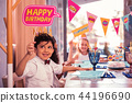 Cheerful little guest smiling and holding happy birthday sign 44196690