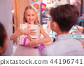 Emotional girl holding the presents and looking at her good friends 44196741