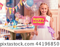 Cheerful girl smiling and holding party sign in her hand 44196850