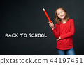 School age girl holding big pencil. Back to school concept. 44197451