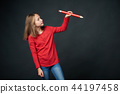 Girl holding big pencil and drawing or writing on blank copy space for text 44197458