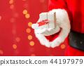 Santa holding a small Christmas gift 44197979
